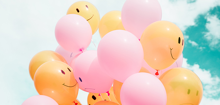 Balloons with happy and sad faces drawn on them